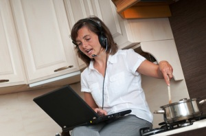 Young-business-woman-having-work-conference-call-from-home-while-cooking-meal-in-kitchen